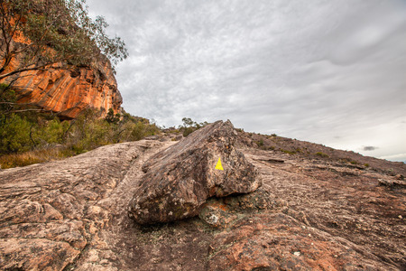 Yellow arrow showing the way on Hollow Mountain walking trek. Grampians National Park, Australia