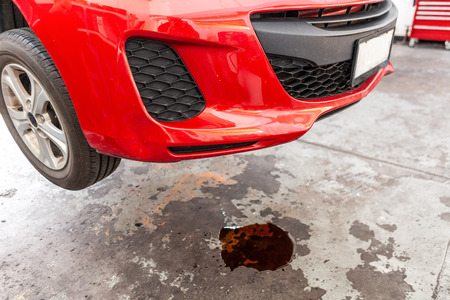Concept of car oil leak depicted with red vehicle and puddle of oil underneath Imagens
