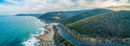 Great Ocean Road passing through scenic landscape in Victoria, Australia - aerial panoramic landscape