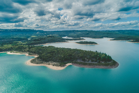 Aerial view of Cardinia Reservoir Lake scenic forested coastline on cloudy day in Victoria, Australia