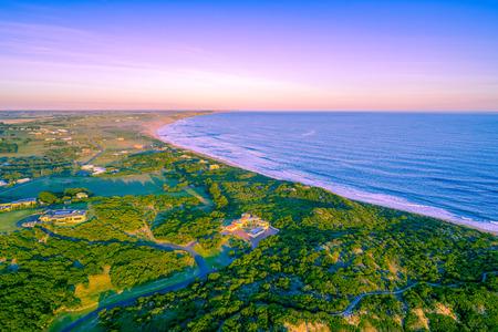Luxury homes on ocean coastline at sunset - aerial view