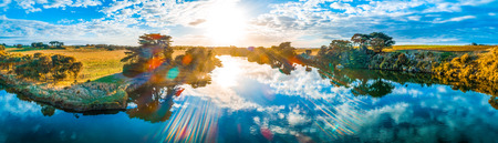 Sunset with sun flare over beautiful river in Australia - aerial panorama