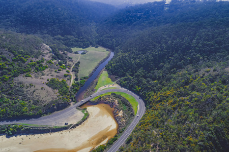 Aerial view of Great Ocean Road bend and forested hills in Victoria, Australia