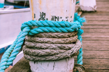 Thick mooring rope on a pier closeup