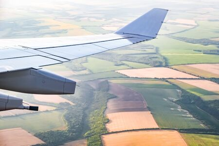 Large wing of passenger jet plane flying over patchwork of agricultural fields in bright sunlight and haze