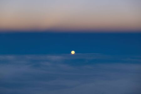 Bright moon high above clouds at night with copy space Stockfoto