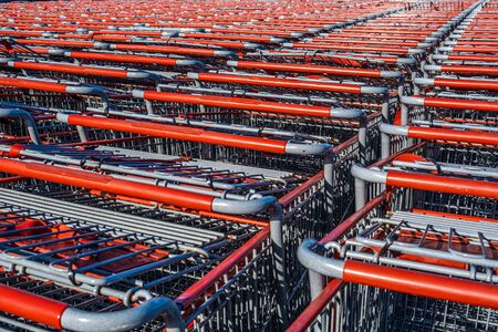 Rows of red shopping trolleys awaiting customers Stockfoto - 128283335