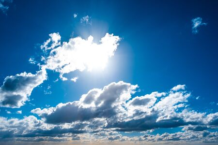 Blue sky with sun shining through white clouds background overlay Stockfoto - 128283395