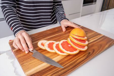 Female hands placed on wooden chopping board with sliced red grapefruit and knife Stockfoto - 128283462