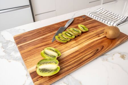 Whole and sliced kiwi fruit on wooden cutting board with knife in modern kitchen