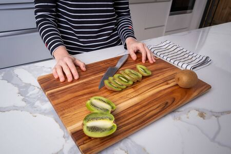 Caucasian woman with chef knife on wooden cutting board with sliced kiwi in modern kitchen interior