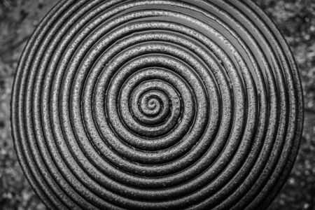Water drops on spiral ornament on a metal surface in black and white