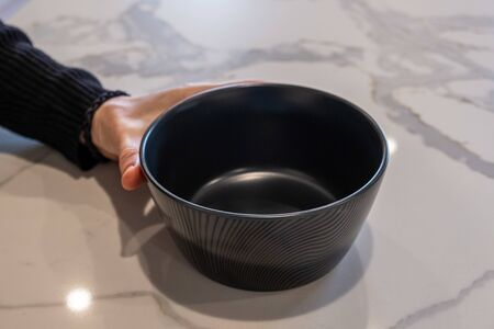 Female hand holding empty black bowl on white marble kitchen top