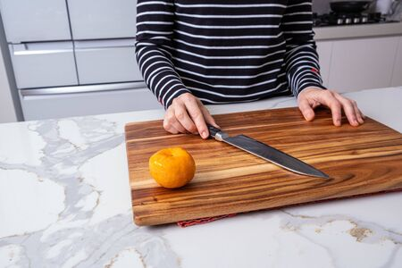 Caucasian female midsection with hands holding a knife on wooden cutting board and clementine in modern kitchen intereior Stockfoto - 128283542