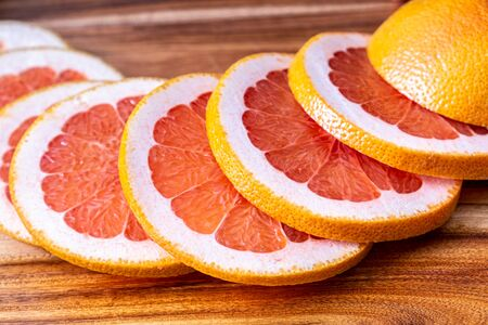 Red grapefruit slices on wooden cutting board Stockfoto