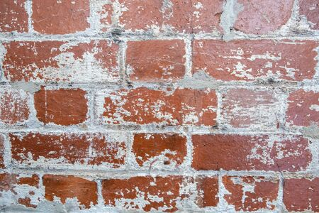 Retro red brick wall with peeling white paint background texture closeup