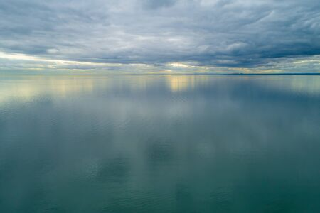 Minimalist seascape of storm clouds over smooth sea at sunset Stock Photo