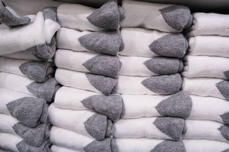 Stack of folded white socks with gray ankles closeup
