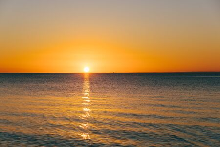 Golden sun touching the horizon over calm sea with copy space Stock Photo