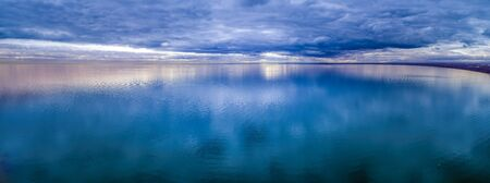 Wide aerial panorama of stormy clouds over smooth ocean water surface Stock Photo