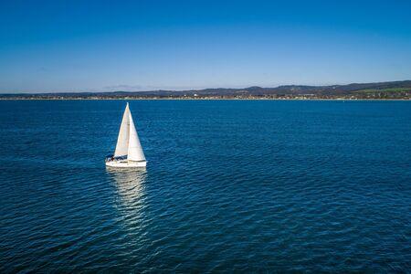 White sailboat navigating Port Phillip Bay near the coastline Stok Fotoğraf - 129925641