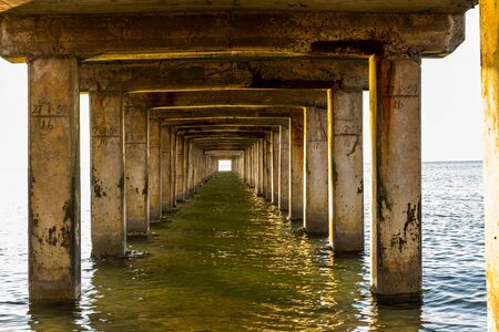 View under a long wooden pier with pillars standing in the water Banque d'images