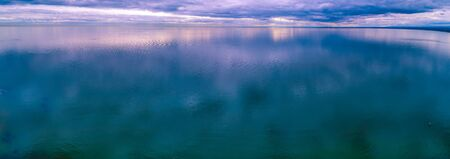 Storm low clouds reflecting in smooth and calm ocean water - aerial panoramic seascape