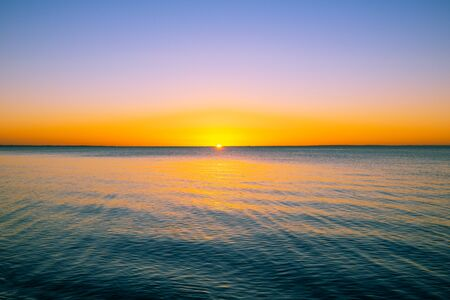 Vivid beautiful sunset - sun almost disappeard behind the horizon over calm sea with copy space