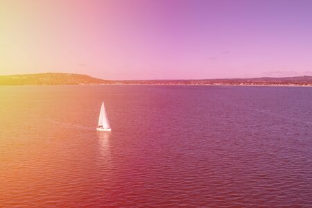 Scenic view of white sailboat sailing near the coastline at sunset Stok Fotoğraf - 129925735