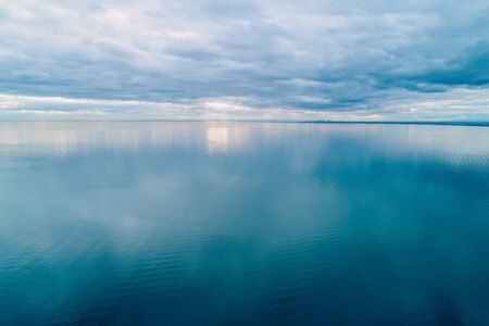 Minimalist aerial seascape. Overcast sky over calm and smooth water surface