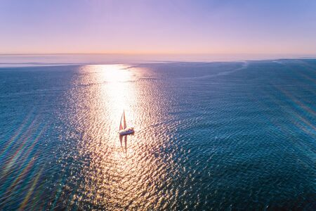 Sailboat in the ocean with strong sunset backlight - minimalist aerial seascape with copy space Stok Fotoğraf - 129925888