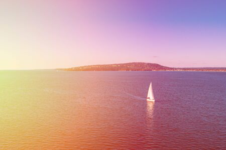 White sailboat sailing across Port Phillip Bay at sunset. Melbourne, Australia Stok Fotoğraf - 129925892