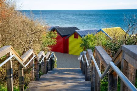 Wooden stairs leading down to iconic Brighton Beach huts on ocean beach in Melbourne, Australia Reklamní fotografie - 129925778
