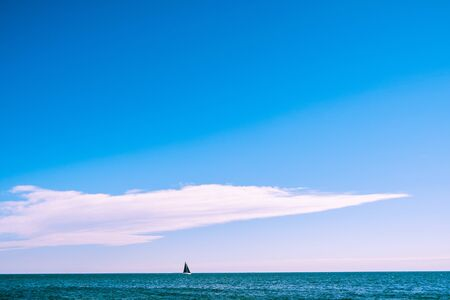 Sailboat with black sail in the sea under blue sky with copy space Stok Fotoğraf - 129925585