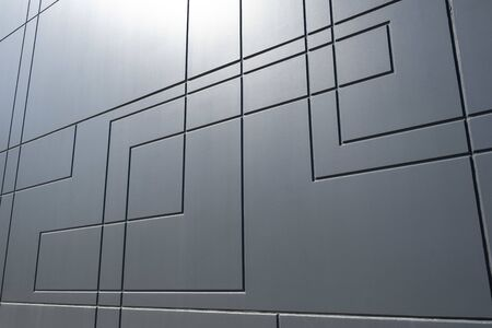 Perspective view of dark gray concrete wall with geometric line pattern in bright sunlight Stockfoto