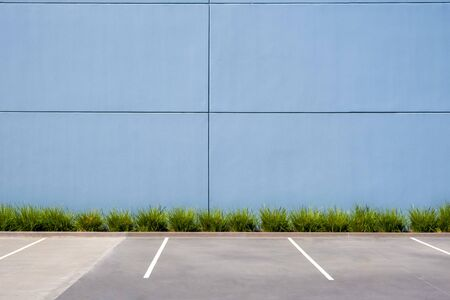 Empty parking spaces against clean concrete wall of an industrial building with pach of grass and copy space Stockfoto