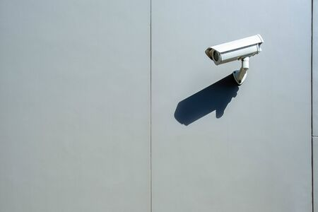 Surveillance wall mounted outdoor camera with harsh daylight shadow and copy space Stockfoto