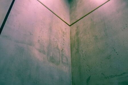 Corner of polished concrete interior wall with colorful lighting and copy space
