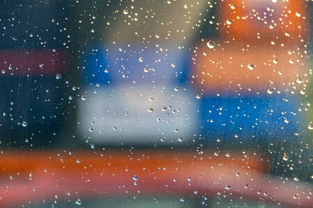 Splashes of blurred color behind window with water droplets - abstract background overlay Stockfoto