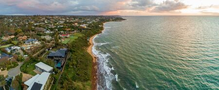 Scenic sunset over ocean coastline with luxury real estate homes and beautiful water at sunset