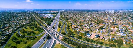 Scenic aerial panorama of highway interchange in greater Melbourne suburbs on sunny day