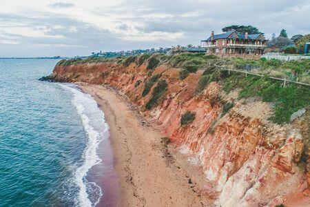 House on a cliff above ocean in Australia - aerial view