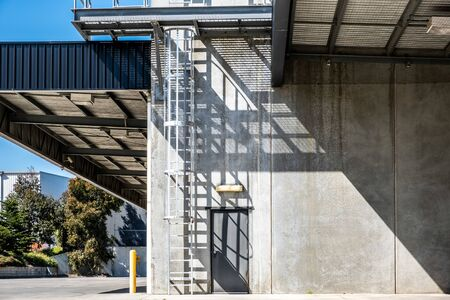 Industrial concrete warehouse back door entrance with emergency fire ladder in bright sunlight and harsh shadows