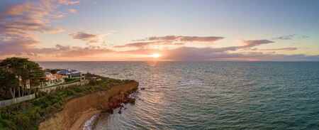 Aerial panoramic seascape of luxury houses on a cliff at sunset Stockfoto