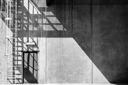 Industrial back door in concrete wall with copy space in bright daylight with harsh shadows