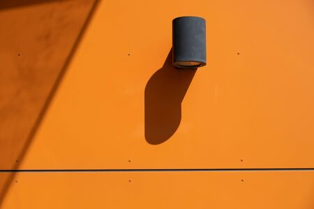 Outdoor spotlight lamp mounted on vivid orange wall of industrial building in birght daylight with harsh shadow and copy space Stockfoto