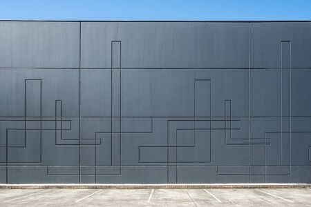 Dark gray concrete wall of industrial building with geometric pattern with empty parking spaces