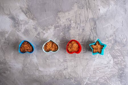 Cupcakes in colorful silicone forms on grungy concrete background - top view with copy space Stockfoto