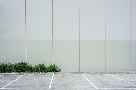 Tall concrete wall next to empty parking with copy space