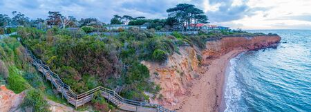 Wooden stairs descending to secluded ocean beach below cliff at sunset. Aerial panorama of Mornington Peninsula, Victoria, Australia